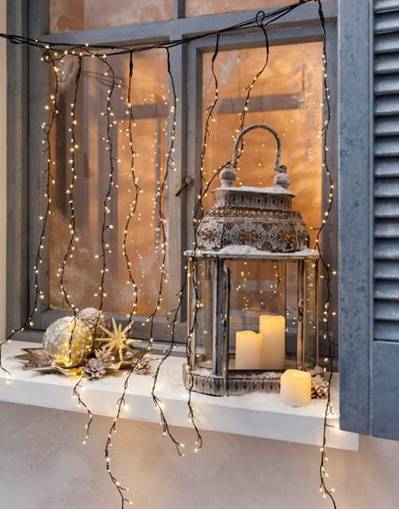 coole weihnachtsdeko idee für festliche fensterdeko außen mit alter laterne metall, weißen led-kerzen, goldenen weihnachtskugeln und regen-lichterkette