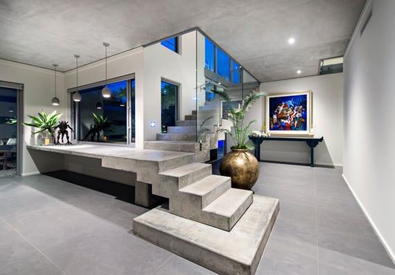 coole raumgestaltung eingangsbereich mit betontreppe, pendellampen über betonpodest, glaswand und elegante zimmerdeko mit amphora vase