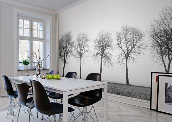 modernes esszimmer interieur im skandinavischem stil mit parketttboden, esstisch weiß, esszimmerstühlen schwarz und akzentwand mit schwarzweißer fototapete bäume
