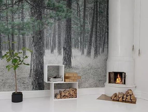 skandinavisches wohnzimmer weiß winterlich gestalsten mit walt fototapete, feuerholz und brennendem feuer im rundem kamin weiß