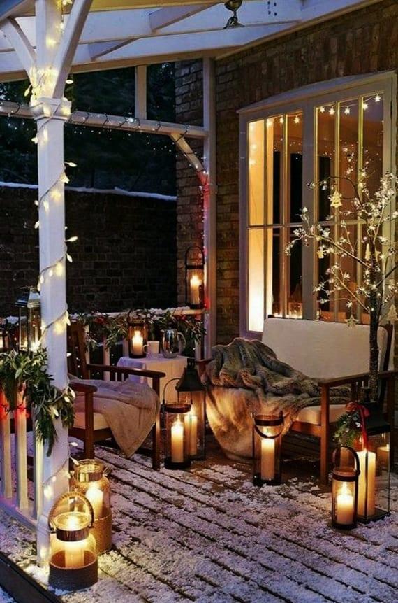 veranda weihnachtlich dekorieren mit tannengrüngirlanden als geländerdeko, lichterkette, kuscheligen decken, glaslaternen und dekorative weihnachtsleuchte-baum