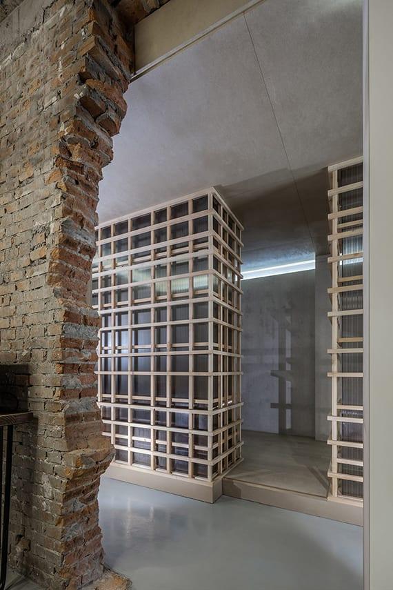 coole raumgestaltung mit poliertem betonboden, wandöffnung in ziegelmauer, moderne trennwände aus holzlatten und kunststoffplatten, betonwände, indirekte raumbeleuchtung