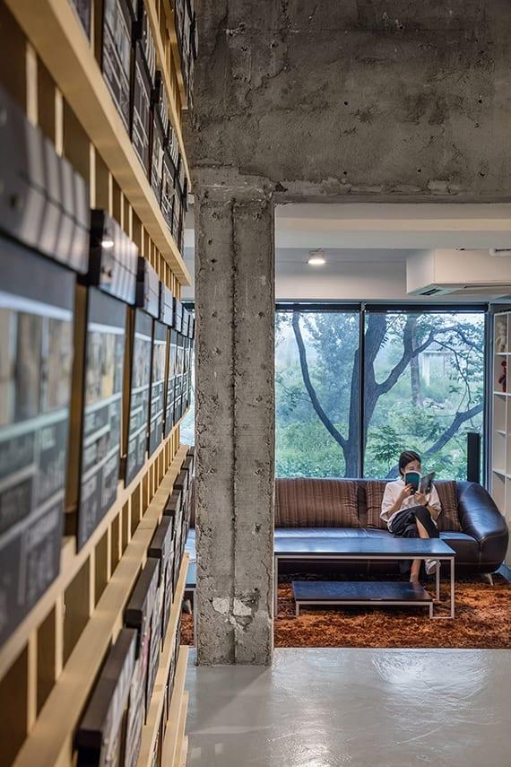 altbau minimalistisch gestalten mit sichtbeton stützen, weißen wänden, raumhohe fenster mit schwarzen fensterrahmen, ledersofa braun und holzcouchtisch auf teppich orange, betonboden weiß, wandgestaltung mit holzlatten