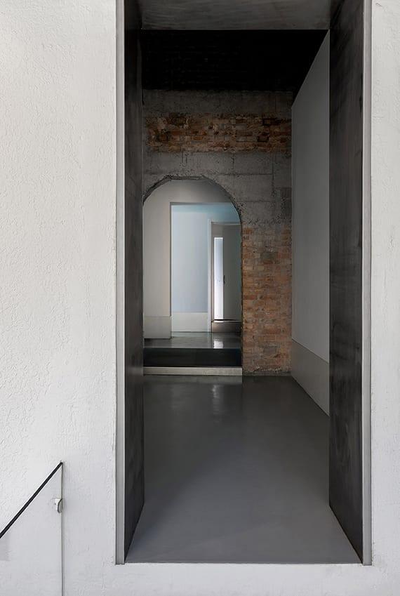 minimalistisches interiuer design mit verschiedenen betonoberflächen, akzentwand aus ziegeln und korridor mit wandöffnungen