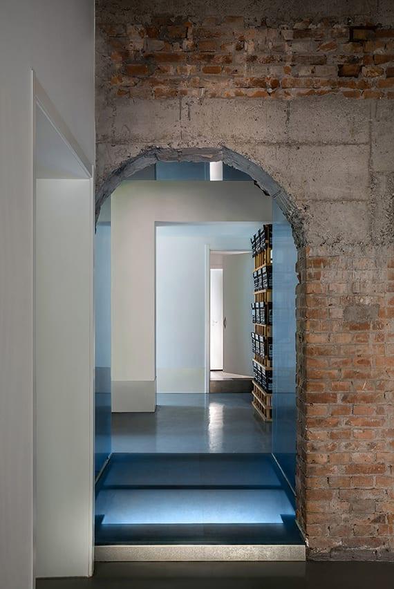 modernes interier und coole korridorgestaltung mit weißen wänden, glasboden, bogenöffnung, ziegelmauer, indirekter raumbeleuchtung, wandgestaltung mit holz