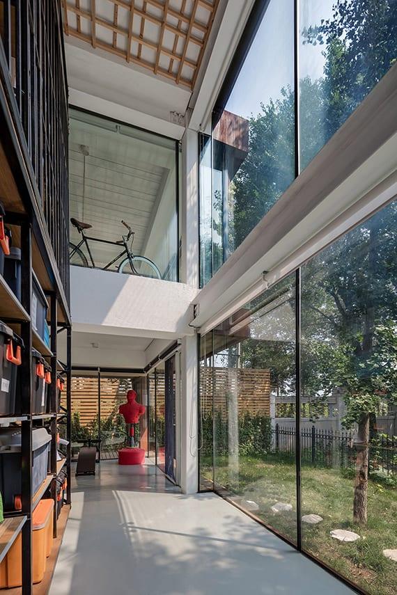 haus renovieren ideen für zusötzliche fläche und natürliche raumbeleuchtung durch glasanbau mit stahlträger, betonboden, sonnenschutzrollos, deckengestaltung mit holzlatten, wandregal stahl