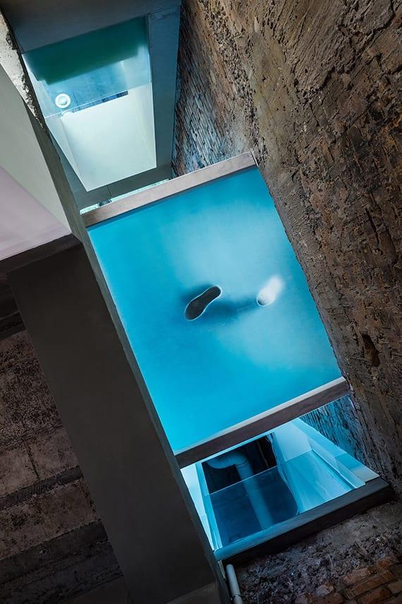 modernes raum- und lichtkonzept für zweigeschoßige häuser mit sichtbarer betondecke und kleiner glasbrücke