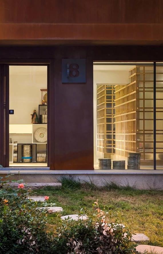 altes haus mit modernem eingang, stahlfassade mit kreativer hausnummer aus metall,schickes interieur mit holzgitterwand, gartenweg mit runden trittsteien zum hauseingang mit glastür
