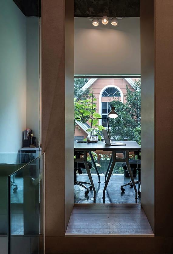 kreative gestaltungsidee für büroräume und homeoffice ohne tür, mit glaswänden, betonboden, wandfarbe weiß