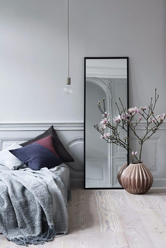 graues wohnzimmer interieur mit dekorative wandverkleidung, pendellampe, modernem standspiegel, bettdecke grau