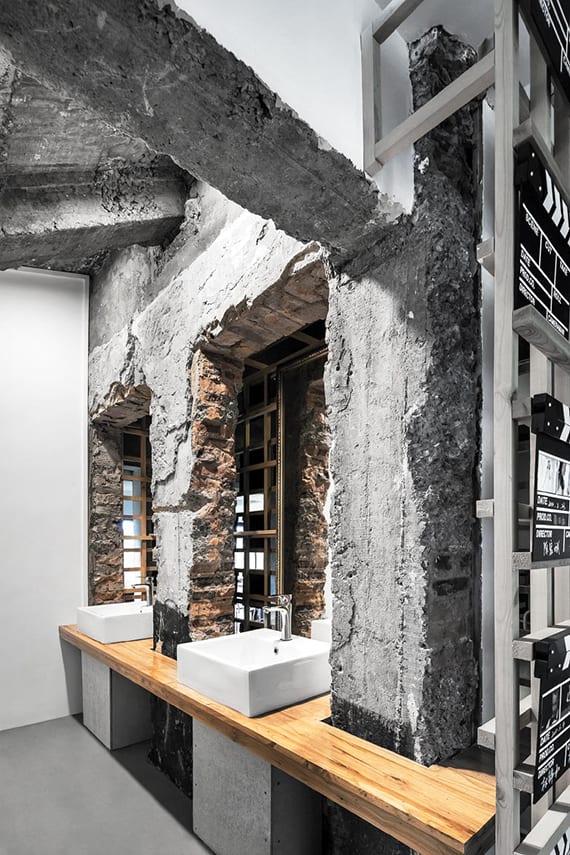 originelle badideen für attraktive badgestaltung mit waschnischen in alter ziegelwand, aufsatzwaschtisch holz mit weisen waschbecken, betonboden, weiß gestrichenen wänden und wandspiegel im goldrahmen an holzgitterwand
