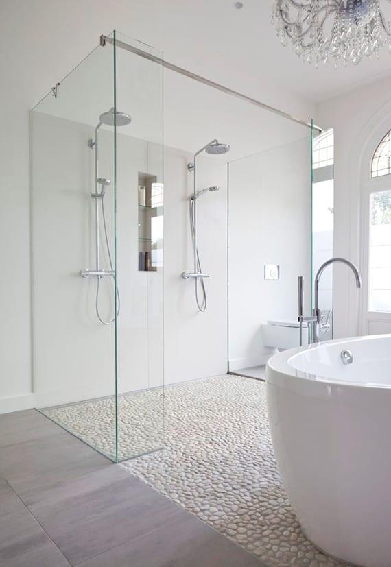 luxuriöses bad mit moderner badewanne weiß, doppel-dusche mit glaswänden und kleiner wandnische,kristall kronleuchter