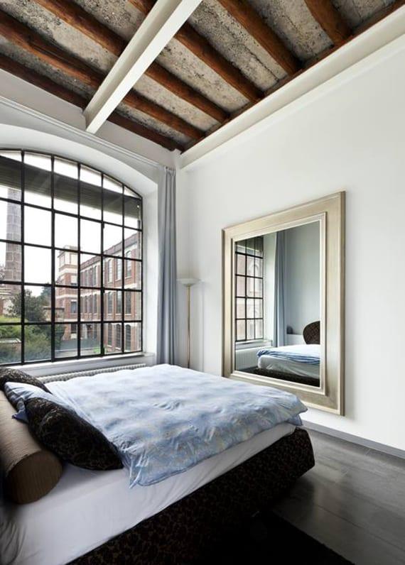 coole gestaltungsidee mit einem rechteckigen spiegel im schlafzimmer, weißen metallträgern, großem bogenfenster mit schwarzem gitter, gardinen grau