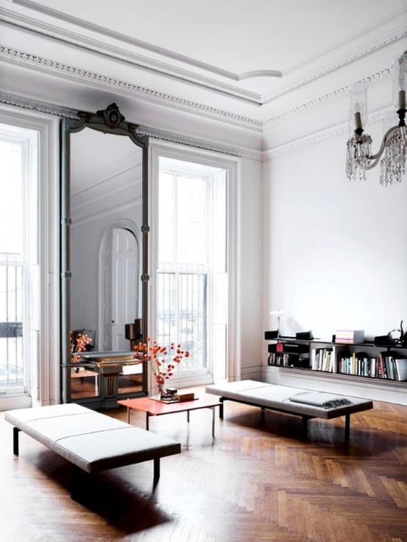 modernes wohnzimmer im klassischen stil mit parkettboden,sitzbänken und rotem kaffeetisch vor fenstern und wandspiegel raumhoch