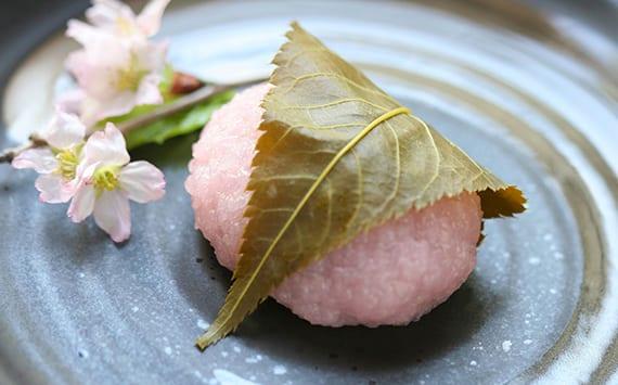 traditioneller japanischer nachtisch aus rosafarbigem reis mit süßer bohnenpaste und kirschblütenblatt