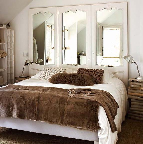 weißes schlafzimmer gemütlich gestalten mit diy bettkopfteil aus holztüren und spiegeln, diy nachttische aus büchern, offene regalsystem, felldecke und dekokissen braun