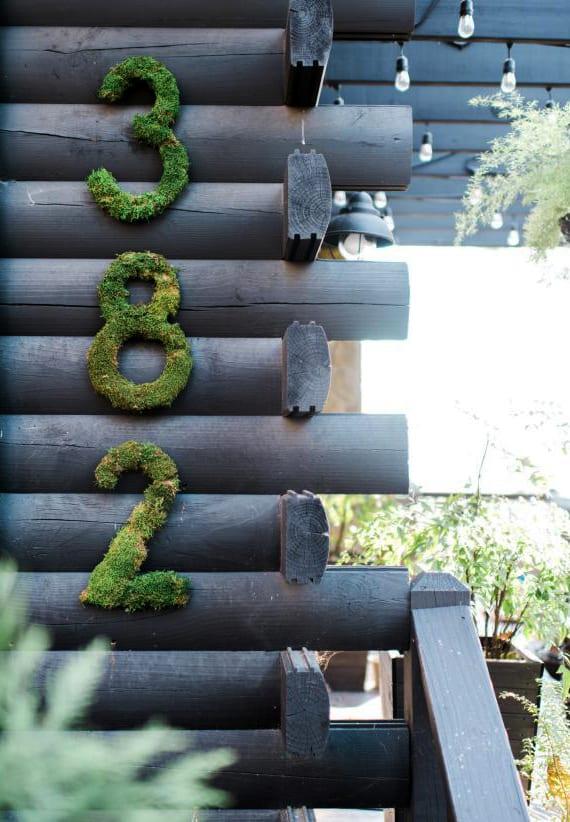 ferienhaus aus rundholz kreativ dekorieren mit selbstgemachter Hausnummer aus grünem moos