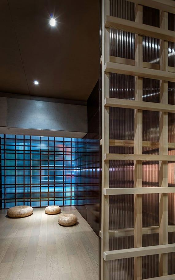 coole raumgestaltung mit holzbodenbelag, trennwänden aus holzgitter und kunstoff für indirekte raumbeleuchtung, asiatisches interieur design mit rattan-bodenkissen
