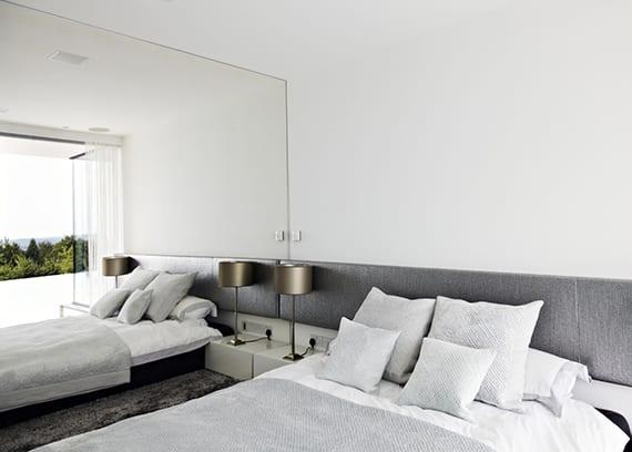 minimalistisches schlafzimmer grau weiß mit ganzflächiger wandspiegel, bett schwarz, teppich und bettkopfteil grau, weiße nachttische mit tischlampen metall