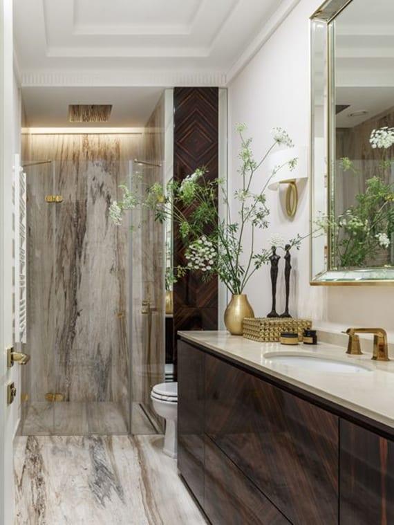 kleines bad mit duschnische, dusche mit glastür,boden und wandverkleidung mit naturstein beige,waschtischschrank holz mit einbauspüle, wandspiegel mit glasrahmen