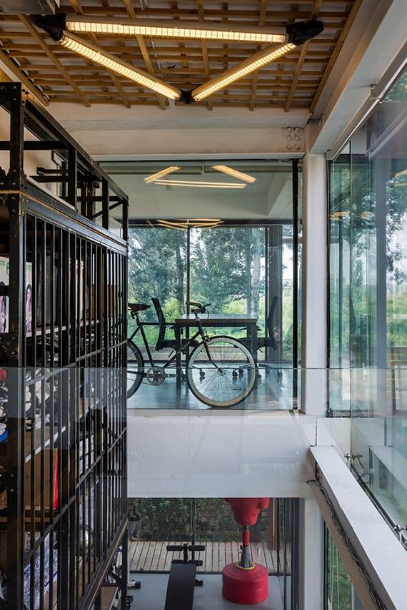 kreative treppenraum gestaltung mit glasfassade, glasinnenwände, wandregalsystem aus stahl, deckenverkleidung mit holzgitter, dreieck-deckenlampe