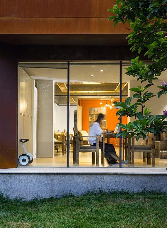 modernes haus mit fassade aus baustahl, überdachter veranda mit fenstern zum innenraum, interieur weiß, akzentwand orange, holztisch-set