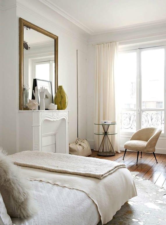 schlafzimmer in weiß attraktiv gestalten mit kamin weiß. holzboden, gardinen und sessel in creme, wandspiegel mit goldrahmen