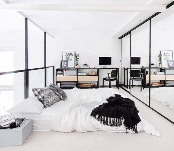 kleines loft-style schlafzimmer in weiß und schwarz mit einbaukleiderschrank, schiebbaren spiegeltüren, arbeitsplatz, regalsystem metall, glasgeländer mit schwarzem stahlhandlauf und matratze auf dem boden
