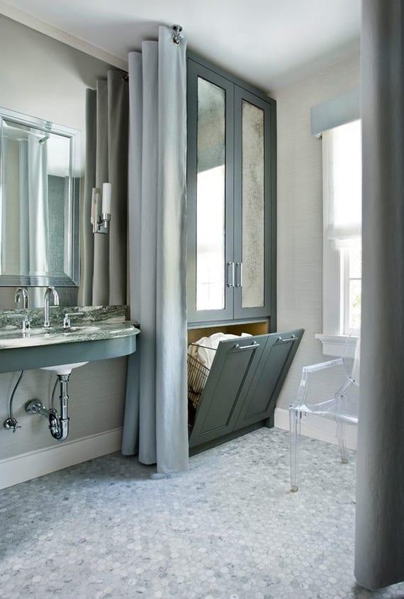 kleines badezimmer in hellgrau und weiß streichen, gerundeter waschtisch mit natursteinplatte, großer wandspiegel,hochschrank grau mit spiegeltüren und ausklappbarem wäschekorb, mosaikboden, gardinen grau