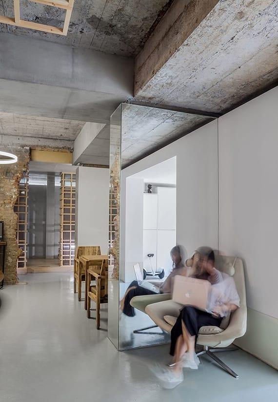 originelle gestaltungsideen und altbau renovieren ideen mit verkleidung von stützen mit spiegeln, betonträger, betonboden grau, weiße wände, deckengestaltung und raumtrennung mit holzgitter, gang im ziegelwand, kreisförmige höngeleuchte
