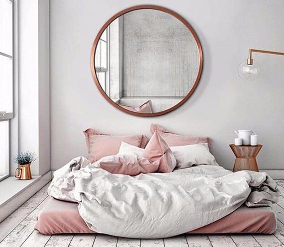 coole schlafzimmer gestaltung mit holzboden weiß, matratze am boden, wandspiegel rund mit kupferrahmen, stehlampe und rundem beisteltisch kupfer, betwäsche rosa und weiß