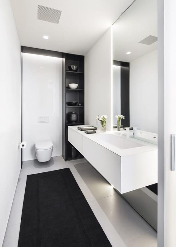kleines gäste-wc weiß modern gestalten mit schwarzem teppichläufer, hochschrank und wandverkleidung schwarz, waschtischregal weiß, großflächigem spiegel und einbauwandleuchte