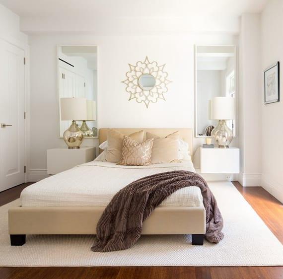 kleines schlafzimmer weiß gemütlich einrichten mit bett in beige, weißen nachttisch regalen mit tischlampen glas, wandspiegeln mit weißen rahmen, dekospiegel rund, teppich weiß, dunklem holzboden