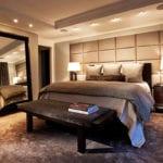 luxus schlafzimmer mit polster wandverkleidung grau, schwarzer sitzbank vorm bett, großflächigem standspiegel mit schwarzem rahmen und einbaudeckenleuchten