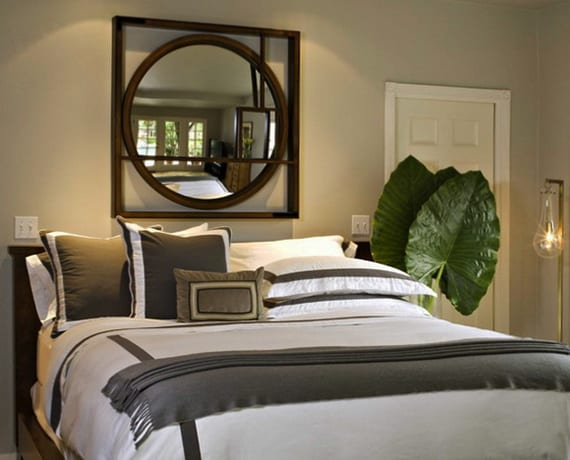 schlafzimmergestaltung mit wandfarbe beige, holzbett, designer stehlampe metall, wanddeko mit spiegel,zimmerpflanze