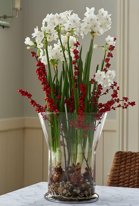 interessante tischdeko ideen frühling mit weißen zwergnarzissen und roten beerenzweigen in glasvase mit kieselsteinen