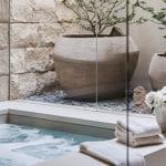 coole badezimergestaltung mit steingarten, dekorative pflanzen in großen runden blumenkübeln, wandspiegel, wandgestaltung mit kalksandsteinen, rechteckiger badewanne und vase mit weißen blumen