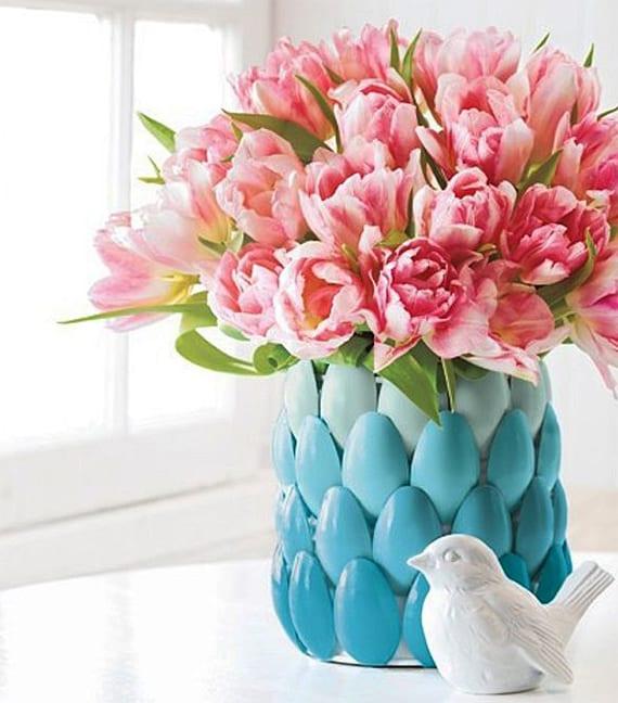 ostern tischdeko idee mit rosafarbigen tulpen in diy blumenvase aus blau gefärbten plastiklöffeln und weißem dekovogel