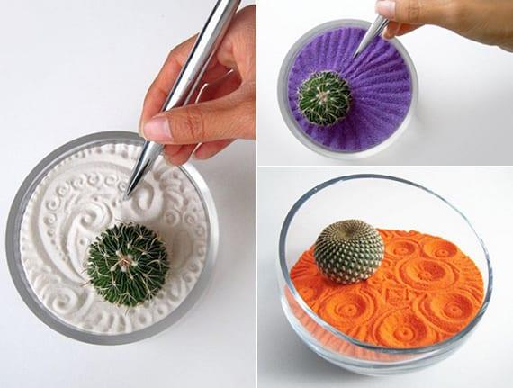 coole dekoidee mit selbstgemachtem zen garten in rundem glasgefäß mit minikaktus und farbigem sand