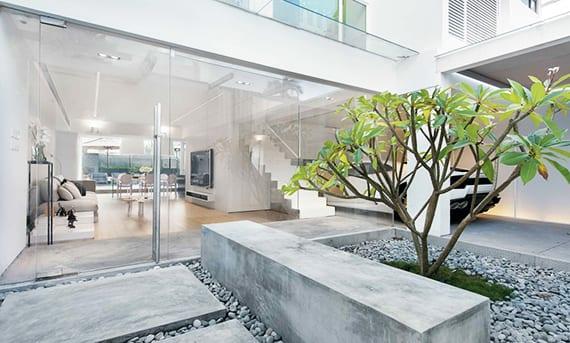 minimalistische gartengestaltung mit offener Garage, gartenweg aus betonplatten, kies und panoramaverglasung zum offenem wohnzimmer mit metalltreppe und essbereich