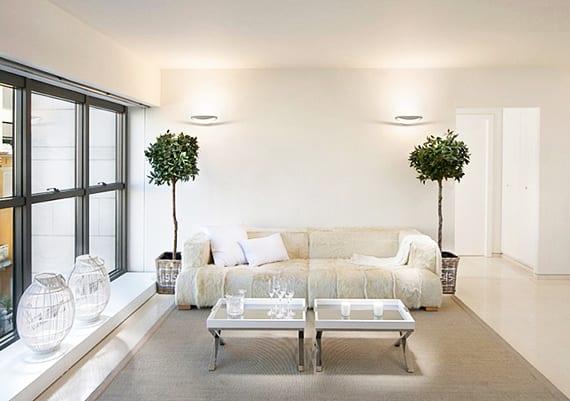 modernes und gemütliches wohnzimmer interieur in weiß mit kugel-lmetalllaternen am fensterbank, 2er Sofa aus Pelz und tablet-couchtischen auf teppich beige,dekorativen bäumen in rustikalen pflanzenkübeln