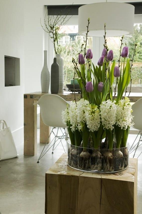 coole  wohnzimmer dekoration mit weißen und lilafarbigen frühlingsblumen in rundem glas als attraktive blumendeko für holzbeistelltisch