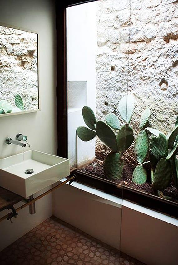 modernes bad mit garten aus kakteen, natürliche beleuchtung durch über dach, aufsatzwaschbecken weiß, wandspiegel und attraktiven bodenfliesen mit muster in beige