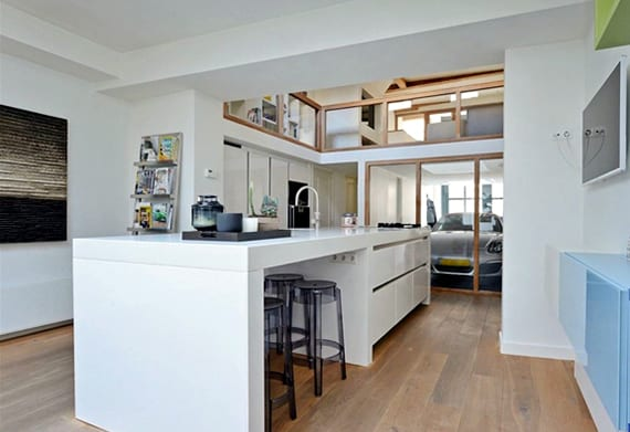 moderne küche weiß mit parkettboden, kochinsel weiß, wohnzimmer über garage mit Porsche Boxster und Verglasung zum innenraum