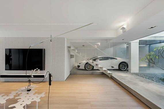minimalistisches wohnzimmer mit blick auf garage, hellem Parkettboden, weißer innentreppe metall, panoramafenster zum zen garten