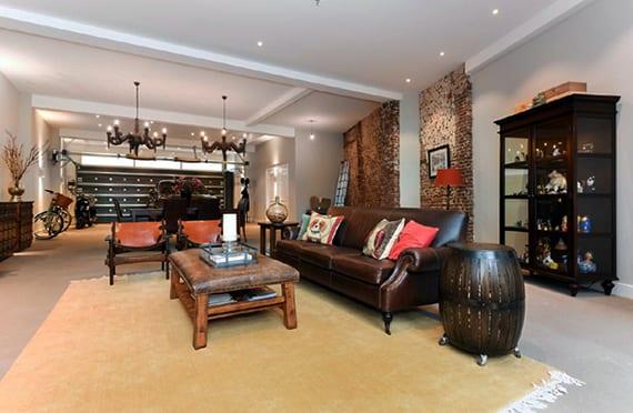 attraktives wohnzimmer interieur mit ziegelwänden, antiken möbeln aus holz und leder und schwarzem porsche cayenne hinter schwarzem garagentor