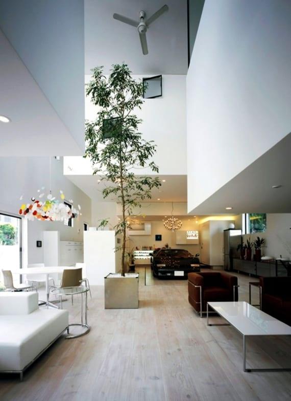 außergewöhnliche wohnzimmereinrichtung mit ferrari schwarz, baum in metallblumenkübel, esstisch rund, offene küche inox, lounge bereich mit leder seats and sofas