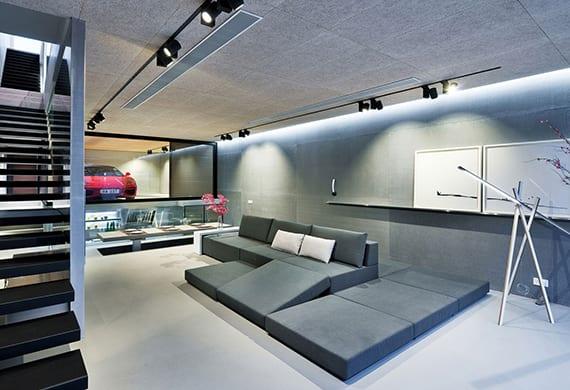 moderne einrichtungsideen für offene wohnzimmer mit küche, essbereich,lounge sofa grau, innentreppe mit schwarzen auskragstufen, panoramafenster zur modernen garage und rotem sportwagen