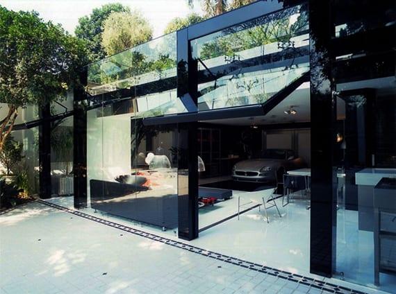 minimalistisches Glashaus mit großen klapptoren aus glas zum garten, offenem wohnzimmer mit wohnküche und essbereich, sportwagen