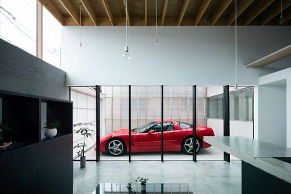minimalistisches Luxus Wohnzimmer mit corvette in glasgarage, holzdecke mit hängenden lampen, schwarzen regalen und kochinsel mit betonküchenarbeitsplatte
